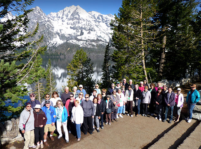 group of travelers posing for picture in front of snow-capped mountains