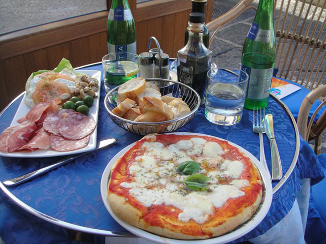 italian pizza and appetizer dish on a blue table