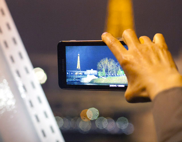 close up of hand holding a phone taking a picture of the eiffel tower at night