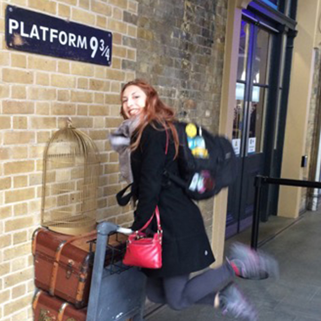 traveler jumping in air at platform nine and three quarters in england