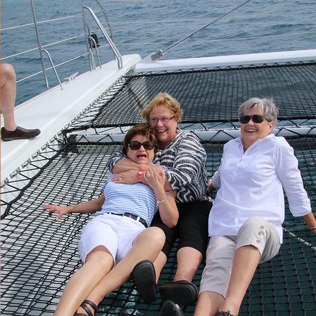 three women sitting on netting on a catamaran boat in spain