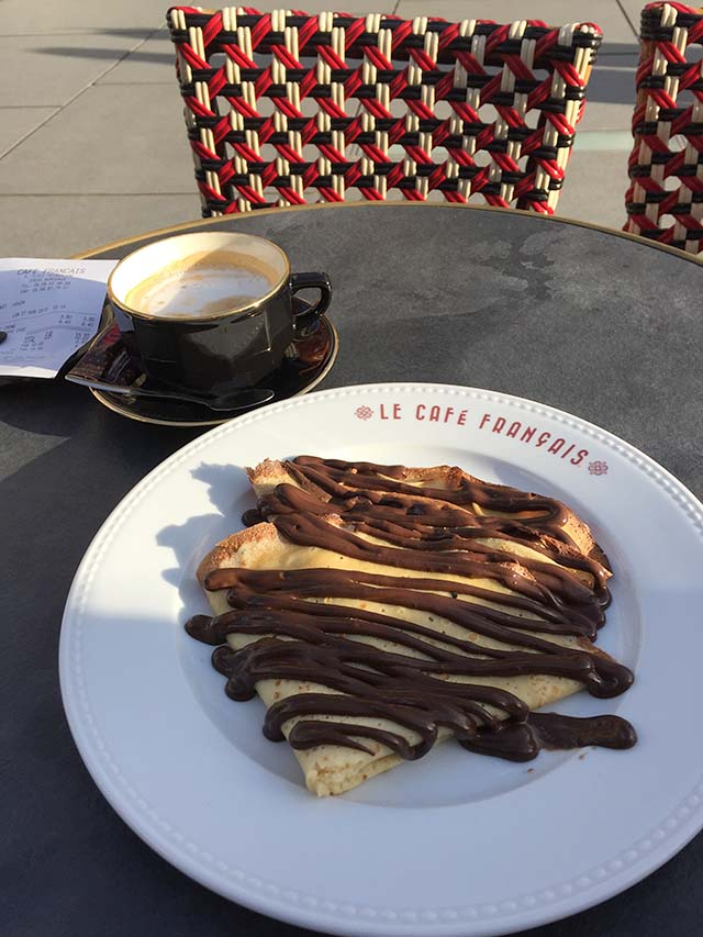 crepes covered with chocolate on a white dish at an outdoor cafe in france