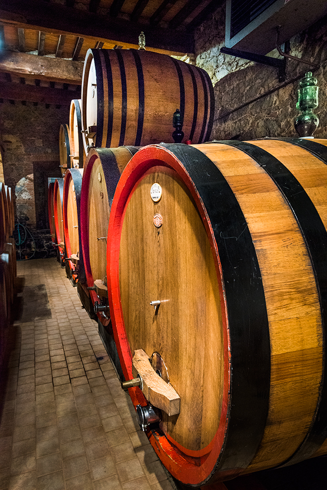 wooden wine barrels stacked up in wine sellar