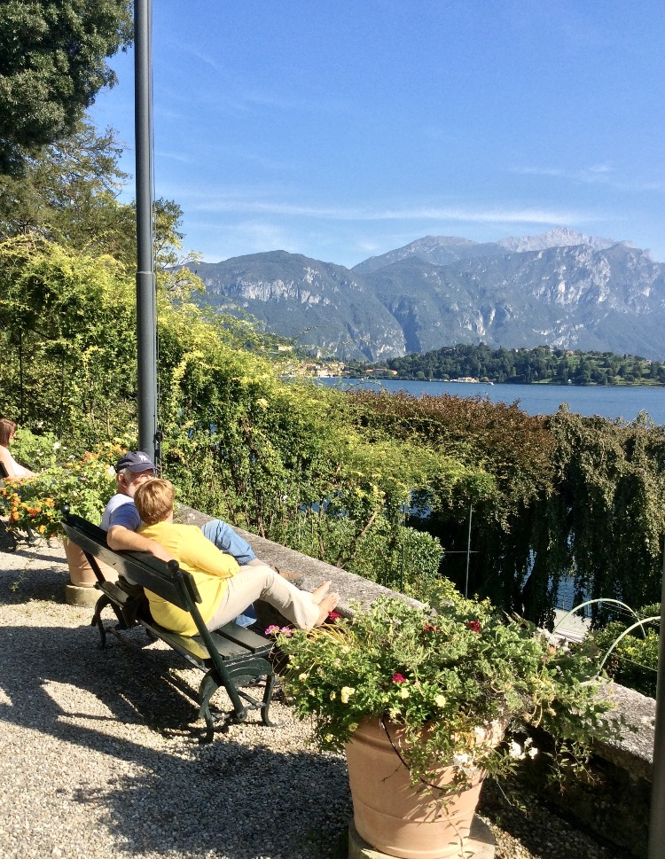 couple sitting on a bench in lake como