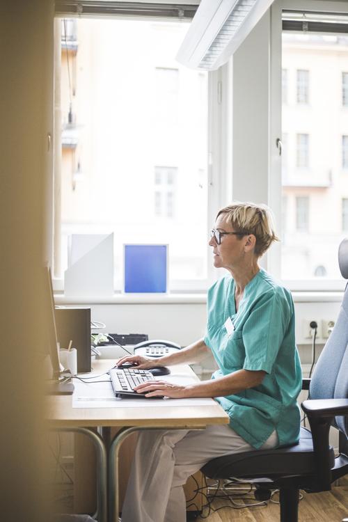 Sjuksköterska med grön överdel och glasögon sitter framför en dator och använder analysverktyget. Det är ett ljust kontorsrum och hon verkar fokuserad