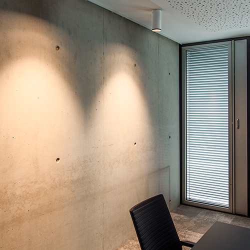 Ceiling luminaire makes concrete wall look cosy