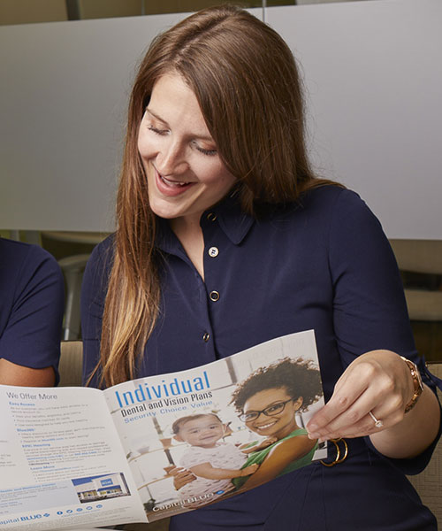 Woman looking at brochure smiling