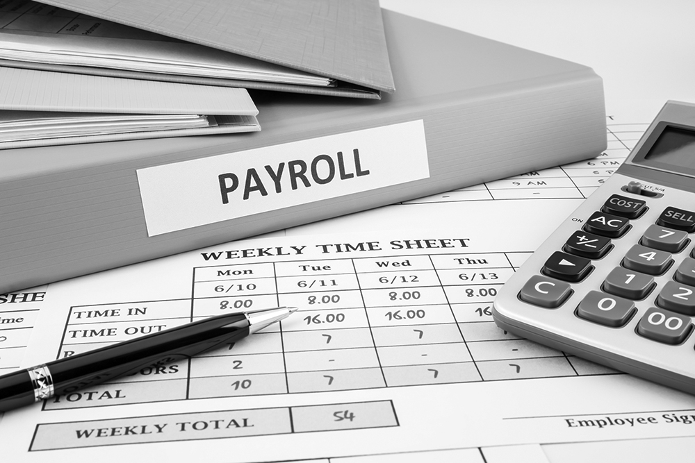 Payroll records sit on a desk near a calculator.