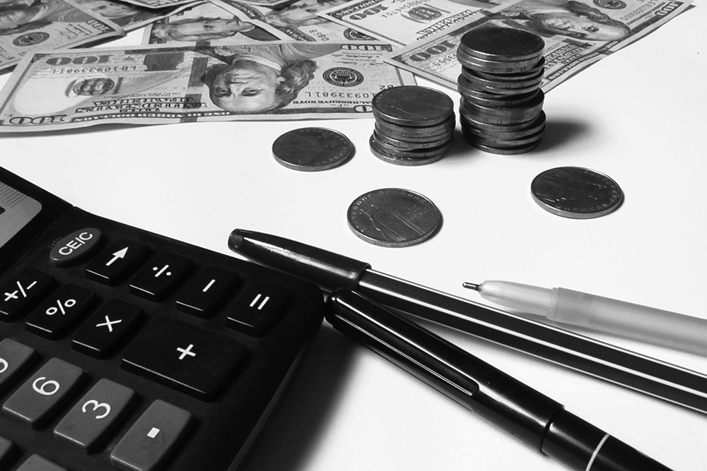 Cash and coins lie near a calculator.
