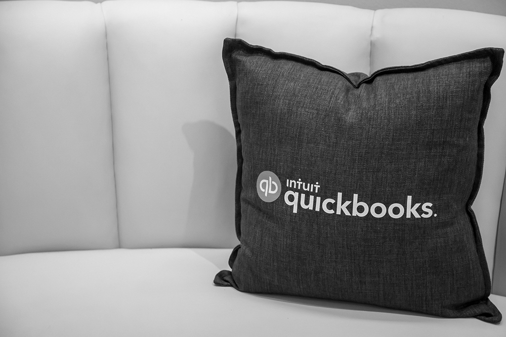 A pillow with the Intuit Quickbooks logo.
