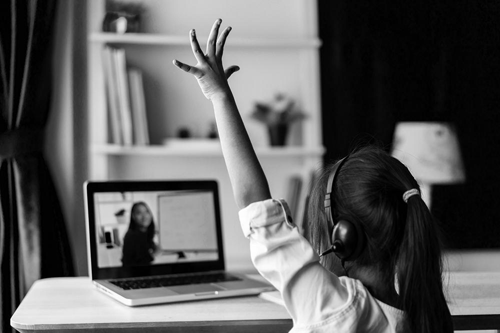 A girl behind a laptop watching an online class raises her hand.