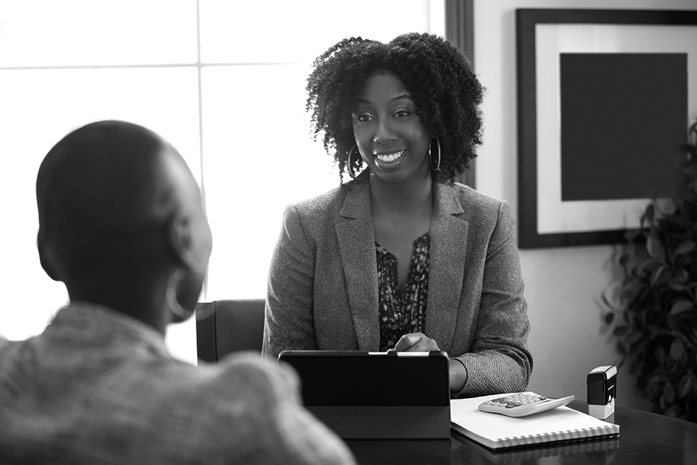 Two African-American businesswomen talking at a desk.