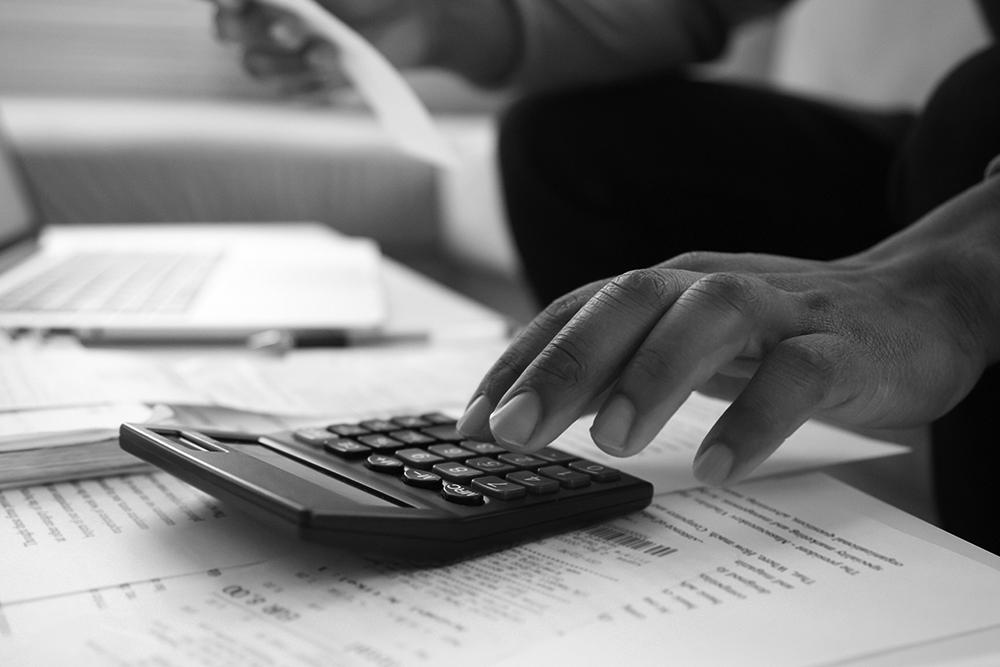 Closeup of a businessman using a calculator.