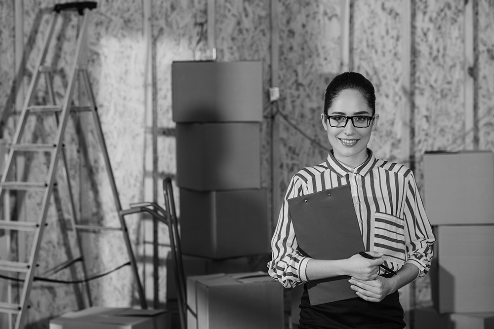 A businesswoman in wearing glasses and a holding a clipboard smiles in front of inventory boxes in a newly constructed room with bare wood framed walls.