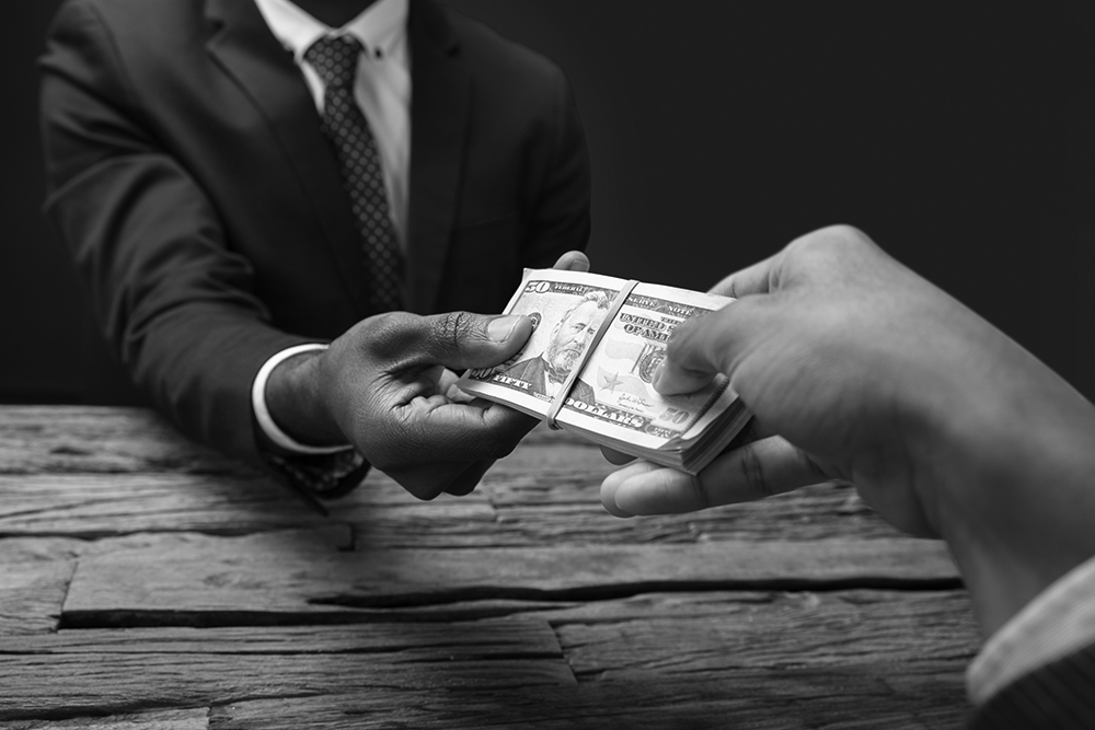 A businessman hands a peer a stack of cash as a loan.