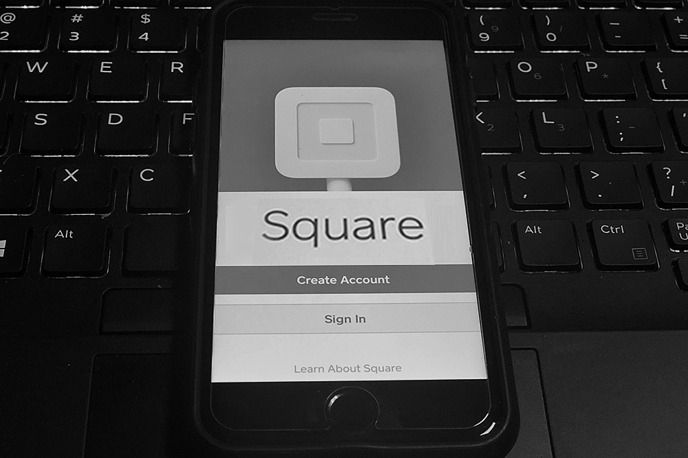 Phone with a Square app on a POS keyboard.
