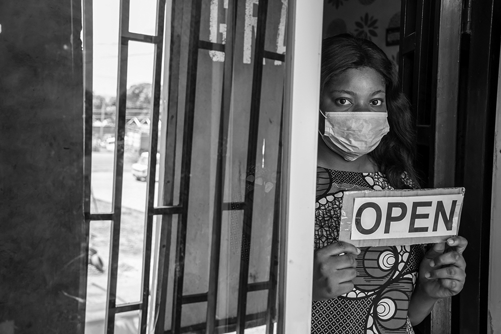 A shop owner wears a mask as she opens her store.