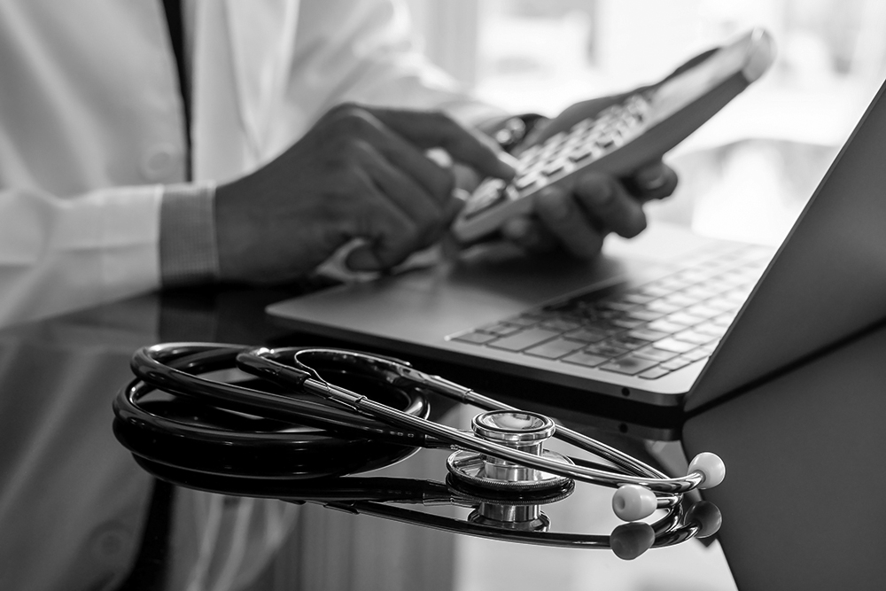 A medical professional in a white lab coat with a stethoscope on the desk uses a pocket calculator.