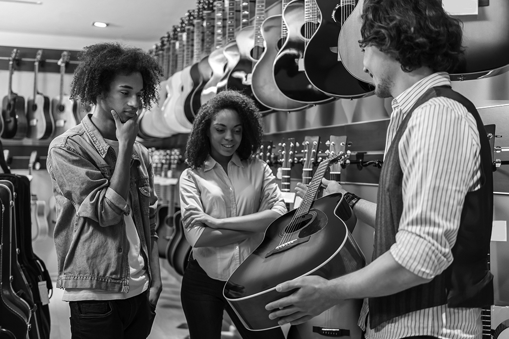 A music store owner shows a guitar to a couple of shoppers.