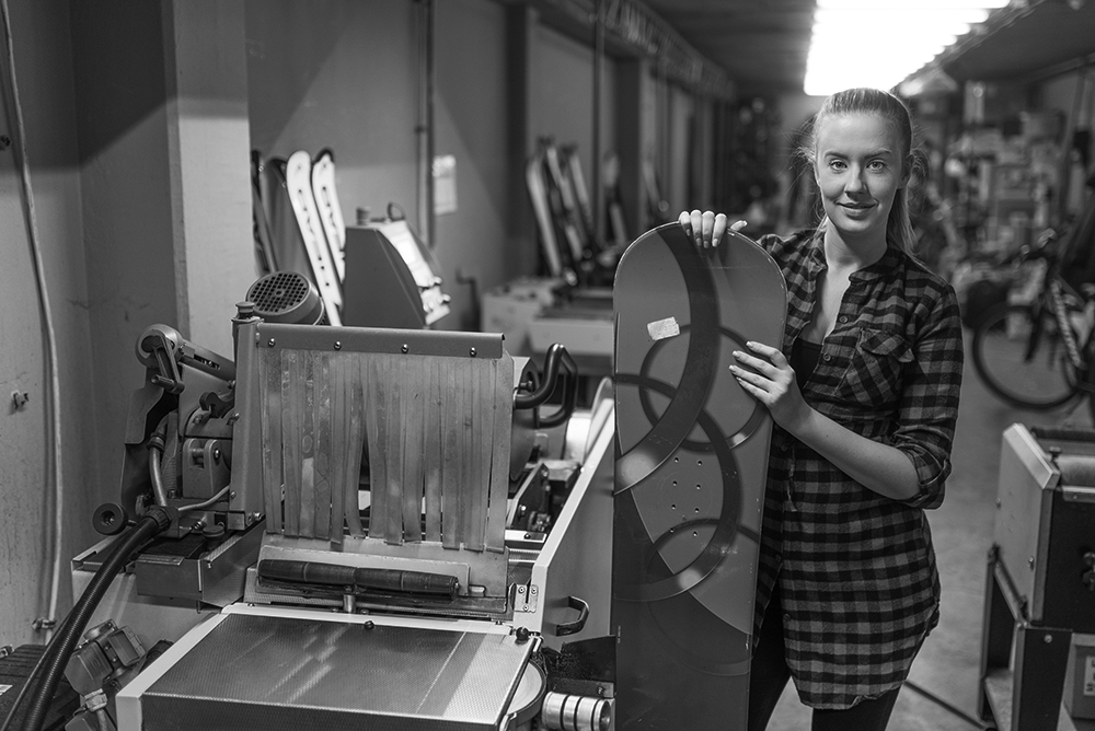 Business woman uses equipment loan financing to purchase a machine for manufacturing snowboards.