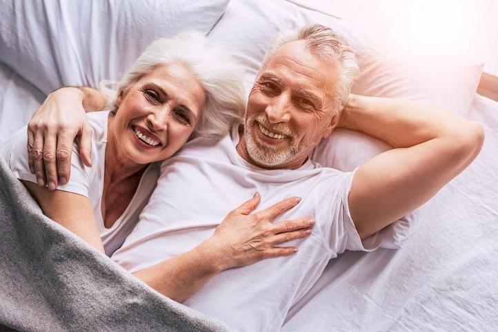 älteres Paar liegt umarmend im Bett