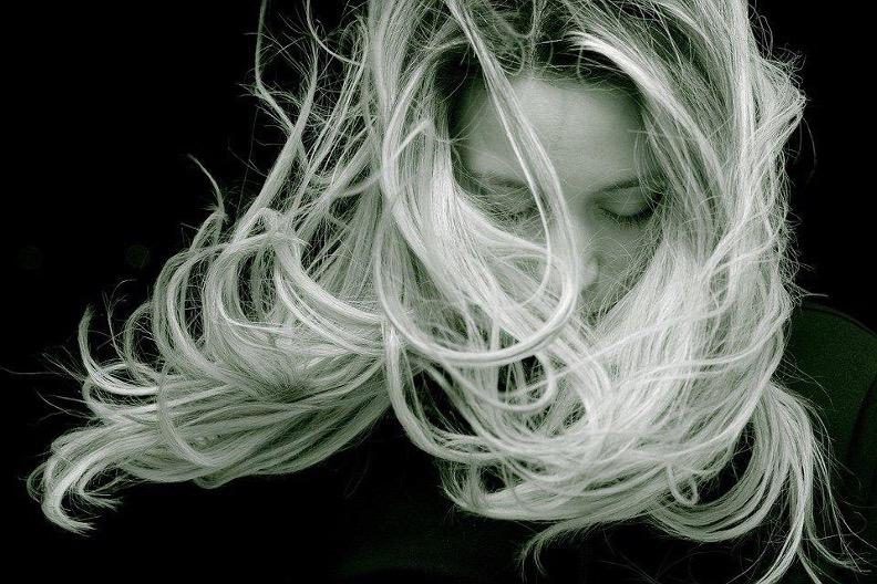 Frau schaut runter und ihre blonden Haare wehen im Wind