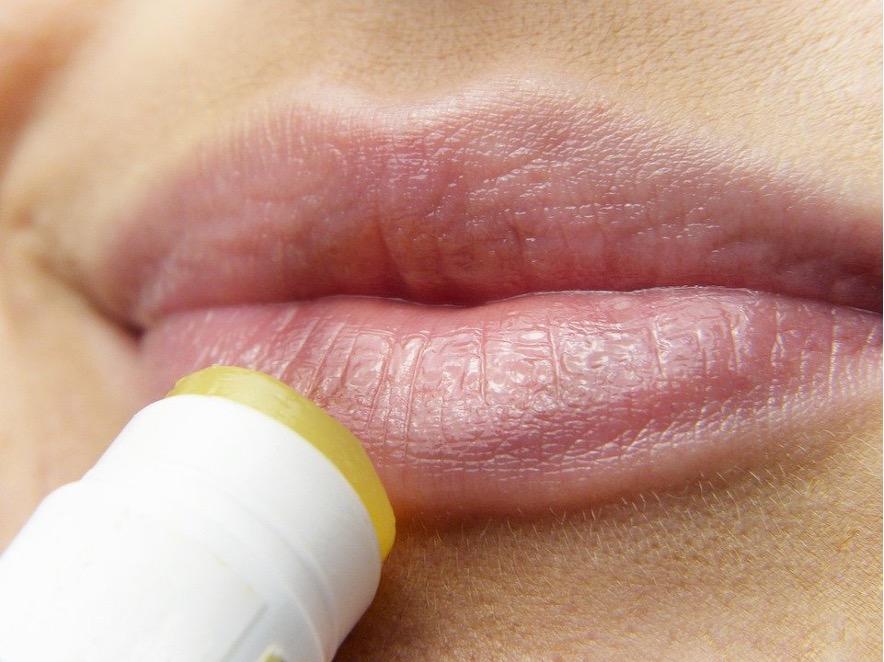 Lippenbalsam wird auf die Lippen aufgetragen