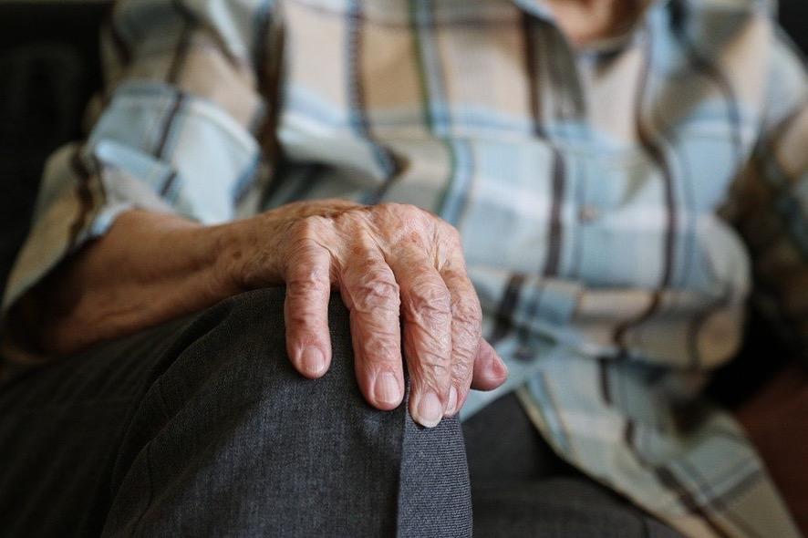 männliche und alte Hand auf dem Knie abgelegt