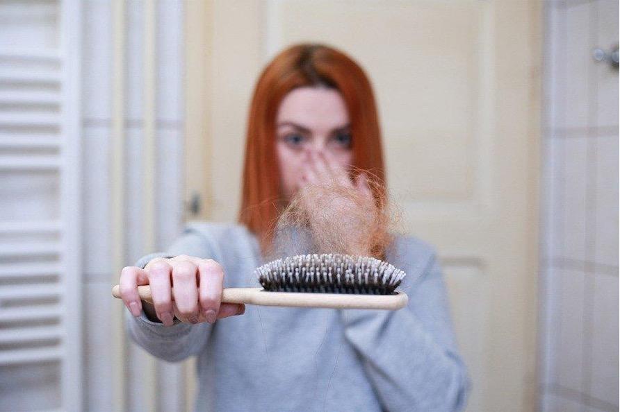Frau mit roten Haaren hält erschrocken einen Kamm mit einem Haarbüschel in der Hand