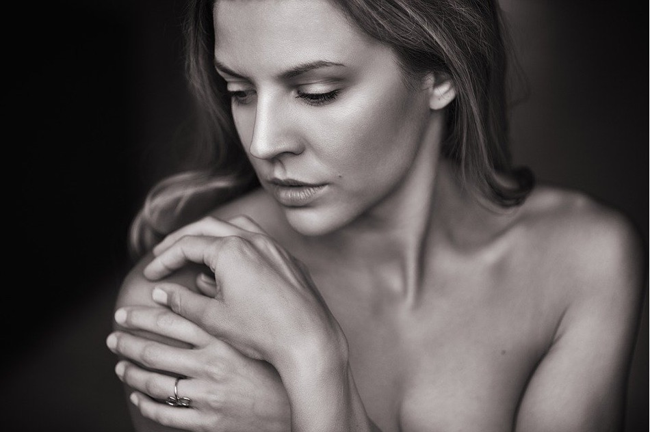nackte Frau hält sich mit beiden Händen an rechte Schulter und schaut rechts runter