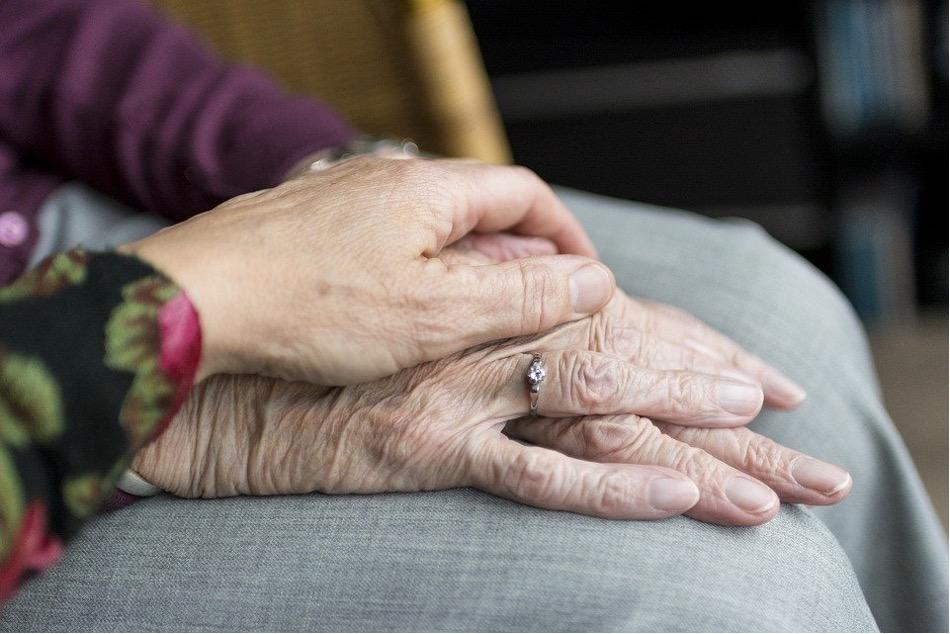 älteres Paar Händchen haltend