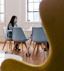 Liikenainen työskentelee pöydällä avoimessa toimistoympäristössä