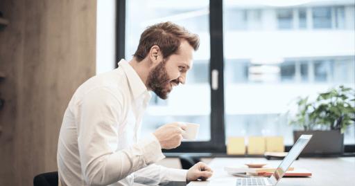 Affärsmannen dricker kaffe och får online-coachning vid sin dator