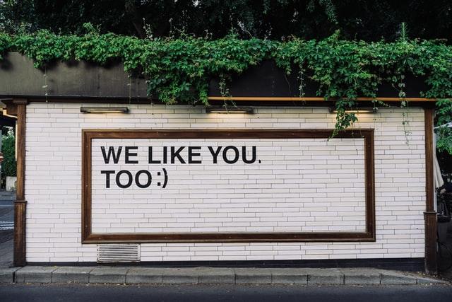 Customer feedback sign on brick wall