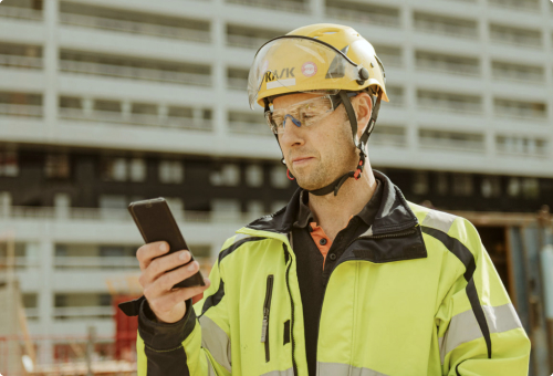Constructionworker looking at phone