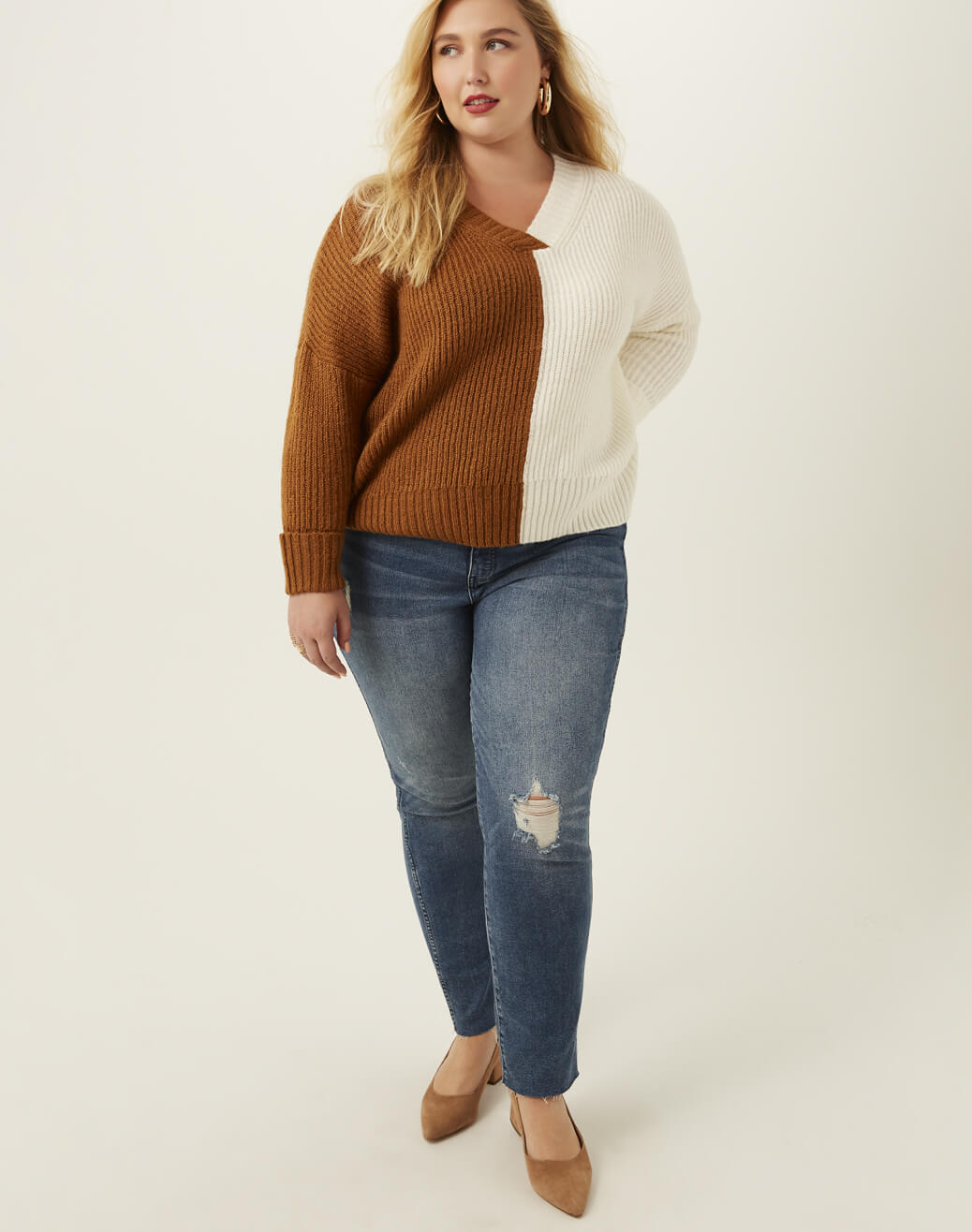 Woman in plus size jeans and brown and white sweater.