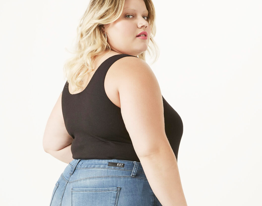 Woman in plus size black tank top and jeans.