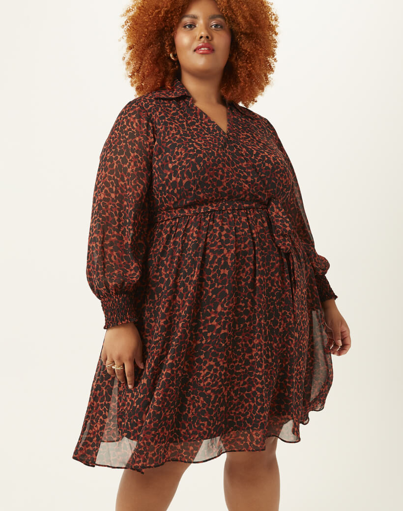 Woman in plus size dark red and black printed dress.