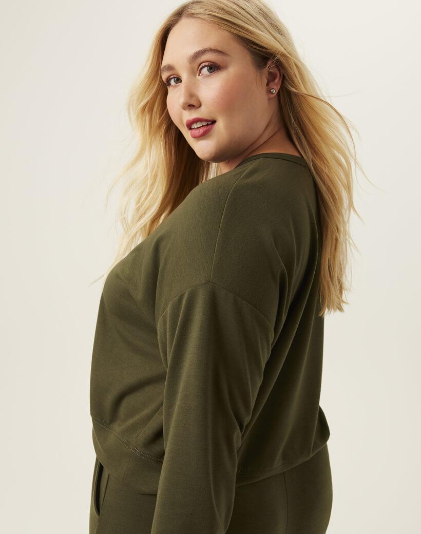 Woman in plus size olive green sweatshirt.