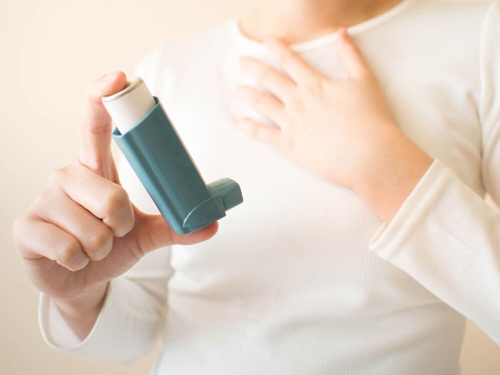 Frau hält Asthma Inhalator in der Hand