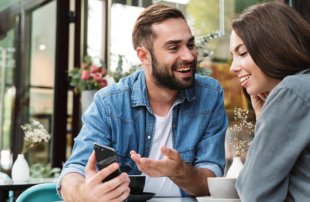 websms - junges Pärchen sitzt im Cafe und freut sich über eine Nachricht am Smartphone SMS Marketing