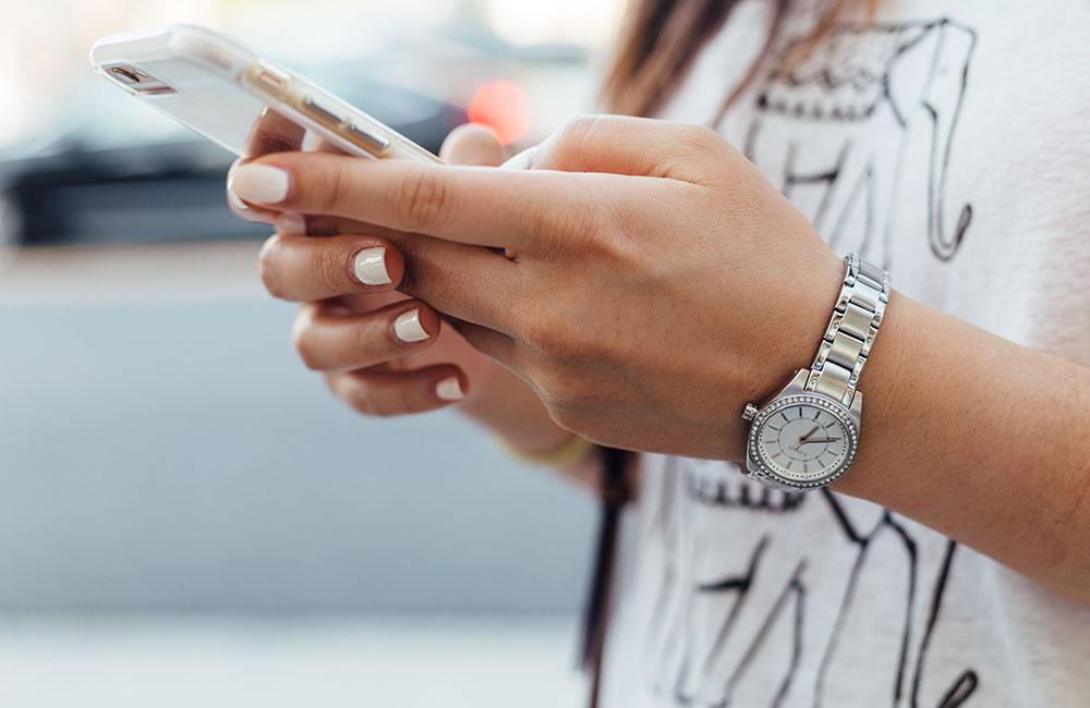 websms - junge Frau schreibt SMS am Smartphone
