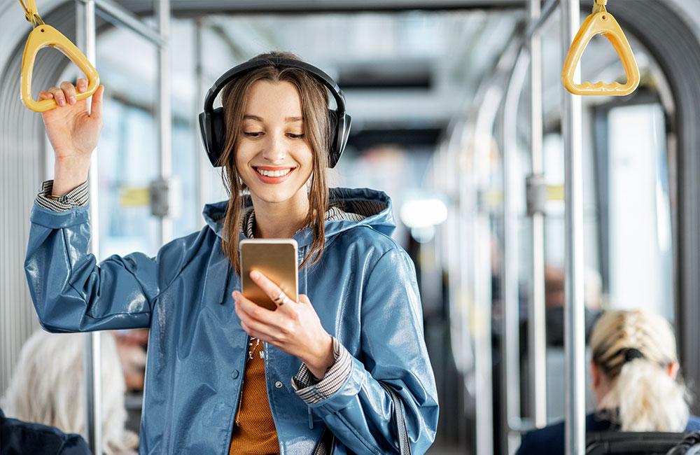 websms - junge Frau fährt mit der Straßenbahn und liest eine SMS auf ihrem Smartphone