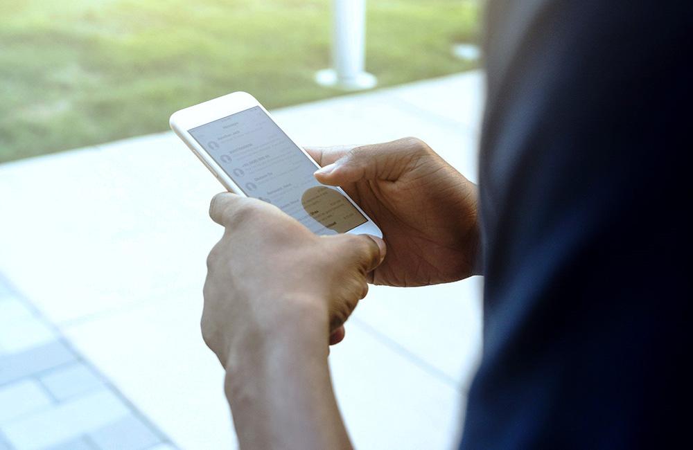websms - Mann liest SMS am Smartphone