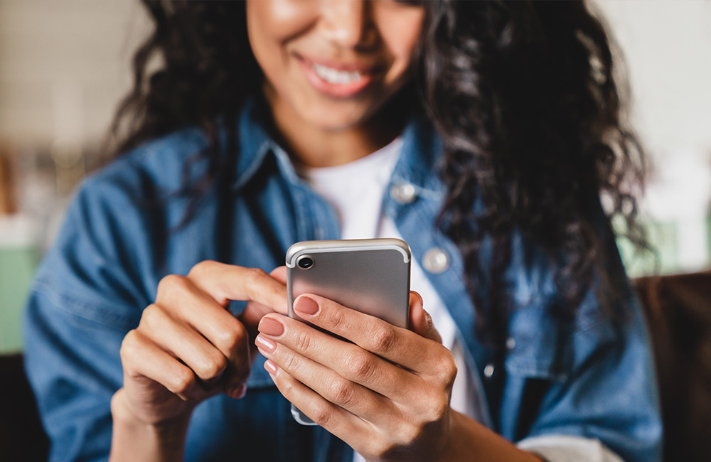 websms - Junge Frau reagiert auf RCS-Nachricht am Smartphone