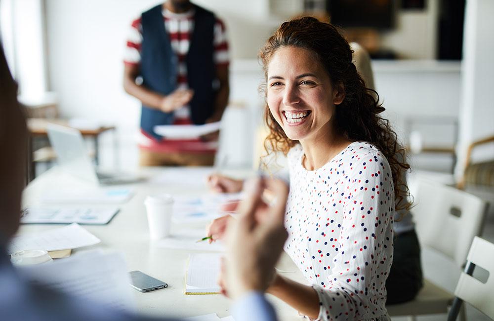 junge Frau fröhlich im Büro beim Vorstellungsgespräch