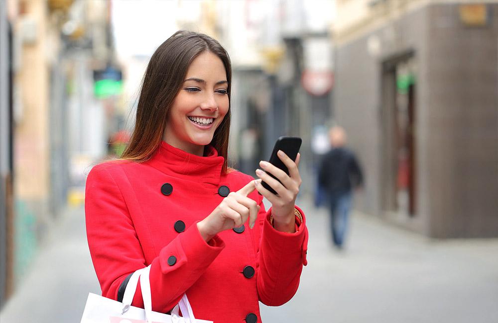 websms - junge Dame freut sich über einen Rabatt-Code mittels SMS