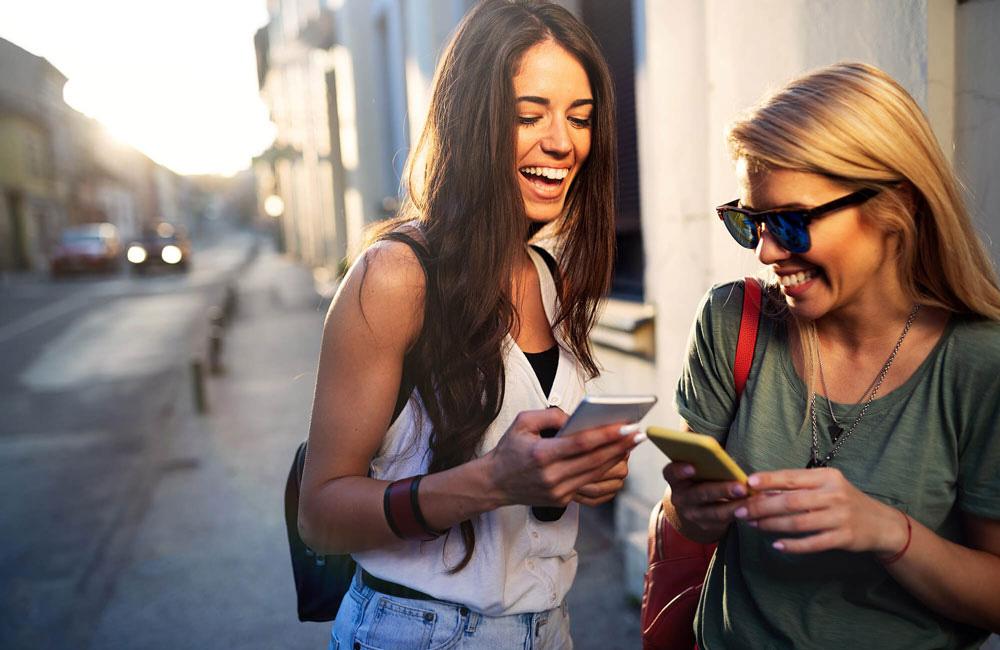 websms - zwei junge Frauen unterhalten sich und benutzen ihre Smartphones