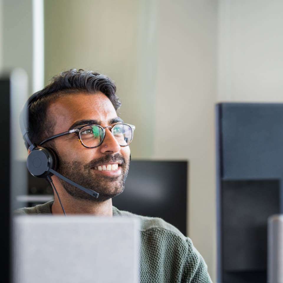 A So Energy customer service operative on the telephone, smiling