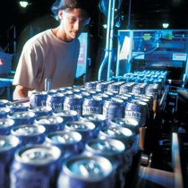 Factory worker running the assembly line for canned Welch's drinks